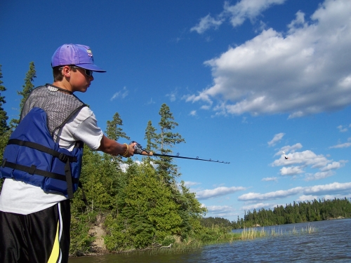 A young guest at Bonny Bay Camp on Wabigoon Lake shows off his fishing technique for landing a trophy catch.
